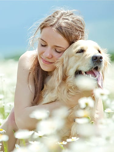 Woman Hugging dog with flowers